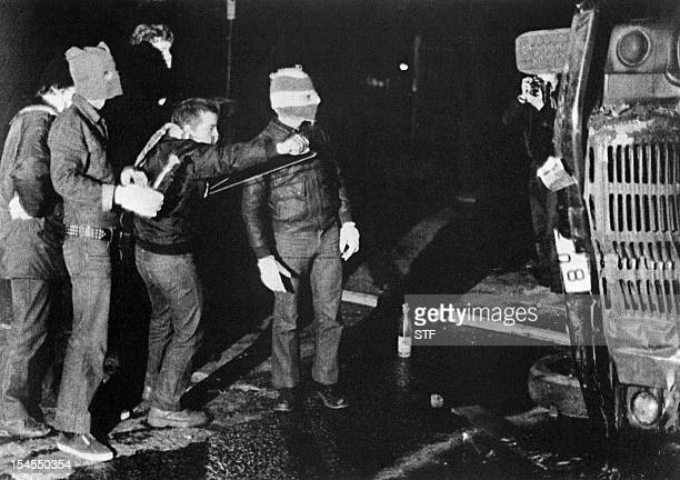 Young people hiding behind an overturned truck face the British army with petrol bombs and slingshots 05 May 1981 in Belfast a few hours after Bobby...