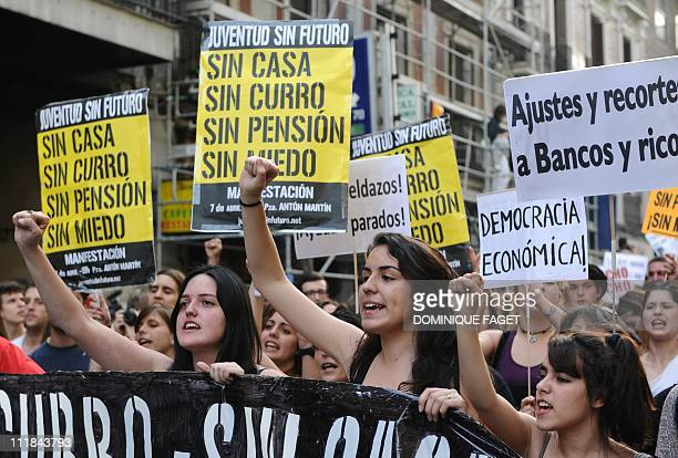 Young people hold placards reading 'Without a house without a job without pension' during a demonstration to protest against insecurity against high...