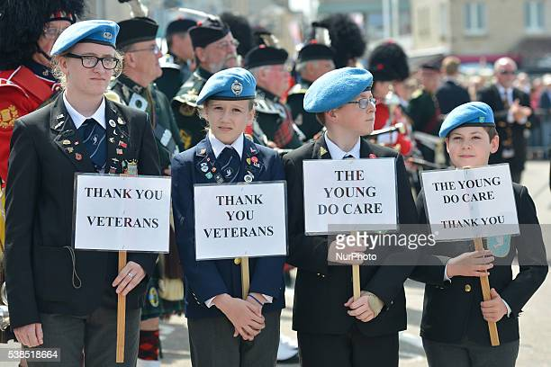 Young people hold 'Thank You Veterans' and 'The Young Do Care' rifflets as DDay and Normandy 1944 British veterans arrive for the Service of...