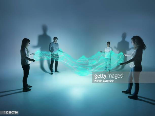 young people holding a lighttrace carpet - projection stock pictures, royalty-free photos & images