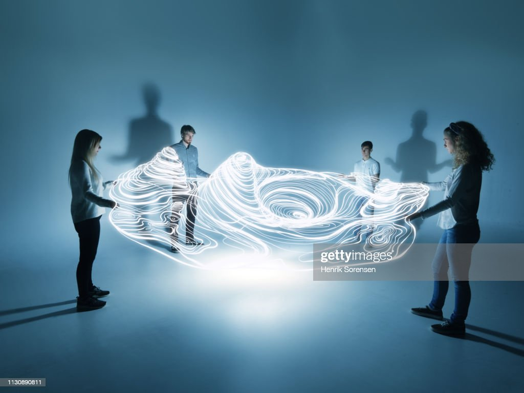 young people holding a lighttrace carpet : Stock Photo