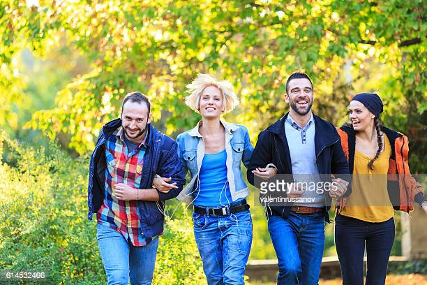 Young people holding hands and walking in park