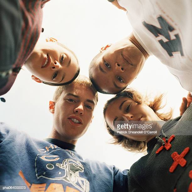 Young people huddling, head to head, view from below, close-up