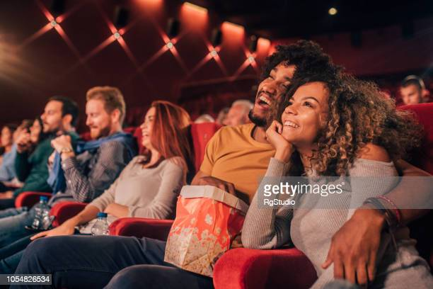 young people hugging at cinema - comedy film stock photos and pictures