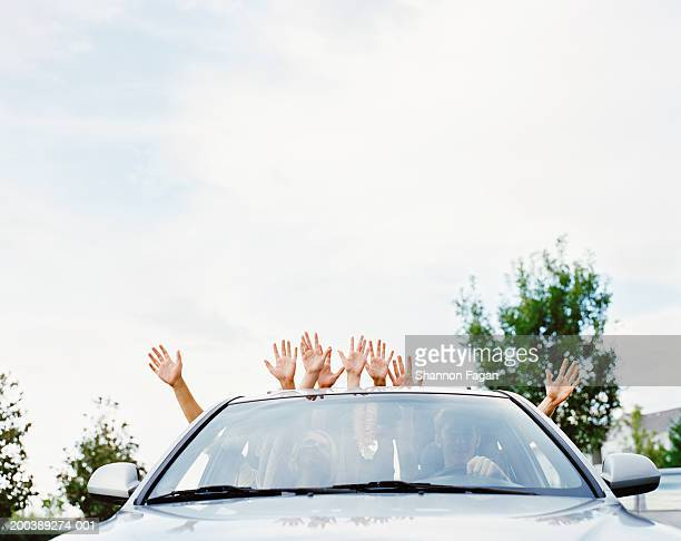 Young people in car sticking arms through sun roof and windows
