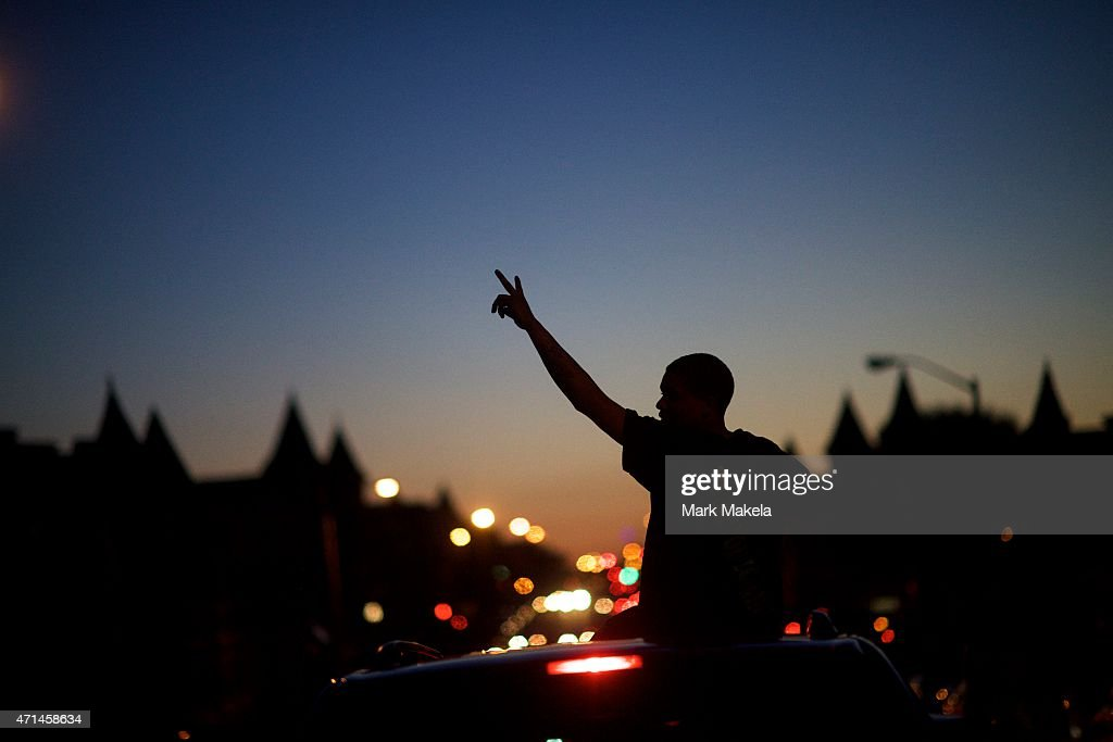 Young people in cars drive towards a phlanx of Baltimore riot police honking their horns and raising their hands with peace signs the night after citywide riots on April 28, 2015 in Baltimore, Maryland. Freddie Gray, 25, was arrested for possessing a switch blade knife April 12 outside the Gilmor Houses housing project on Baltimore's west side. According to his attorney, Gray died a week later in the hospital from a severe spinal cord injury he received while in police custody.