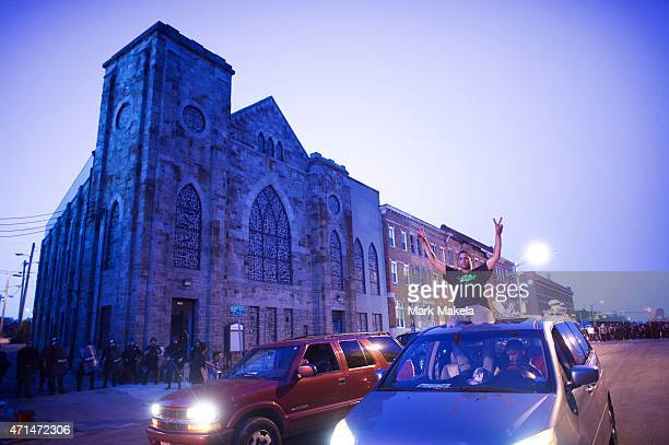 Young people in cars drive towards a phlanx of Baltimore riot police honking their horns and raising their hands with peace signs the night after...