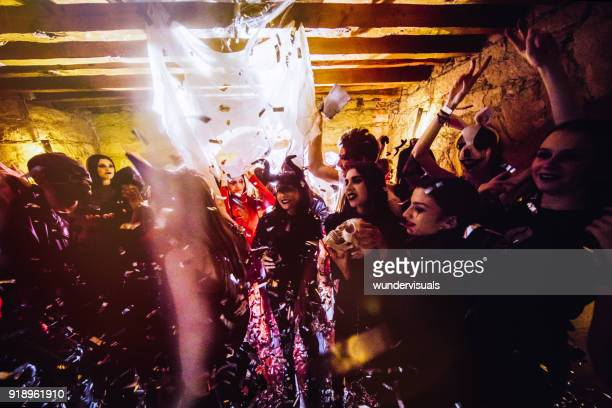 young people in halloween costumes dancing and celebrating at party - halloween party stock photos and pictures