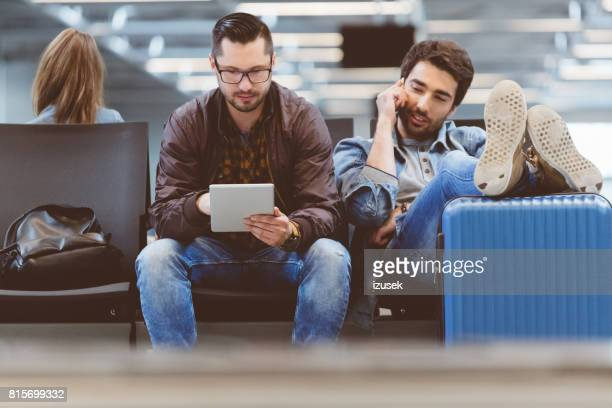Young people in international airport waiting for flight
