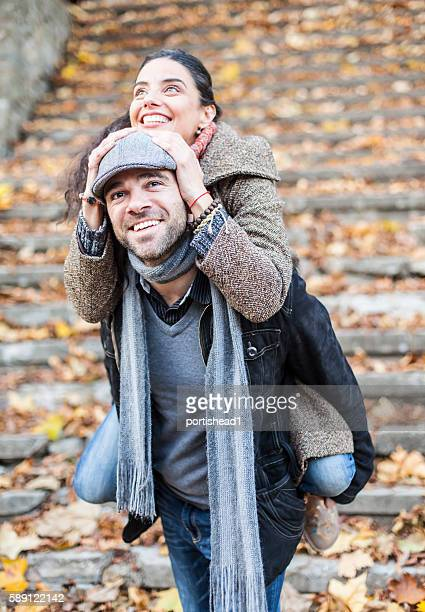 Young people in piggyback ride outdoors