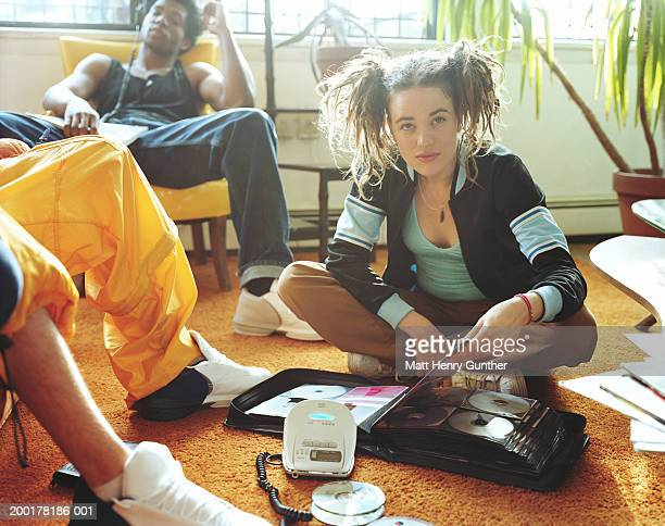 young people in room, woman on floor with cd case, portrait - personal compact disc player stock pictures, royalty-free photos & images