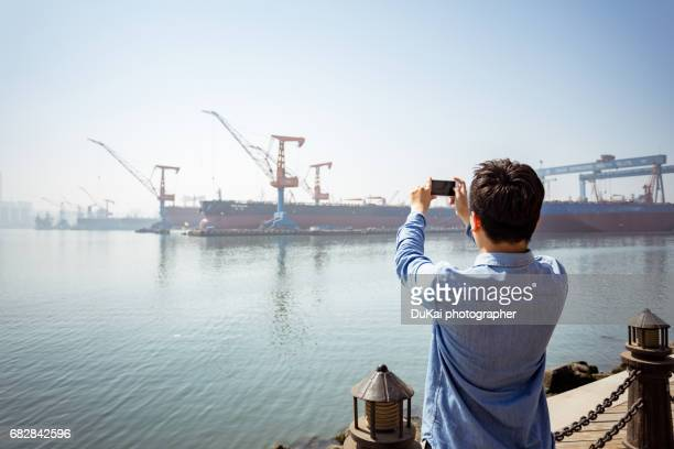 young people in shipyard dock the use of mobile - dalian stock photos and pictures