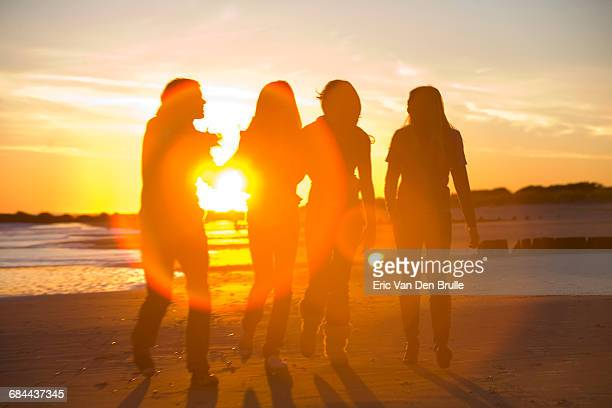 4 young people in silhouette walking - eric van den brulle stock pictures, royalty-free photos & images