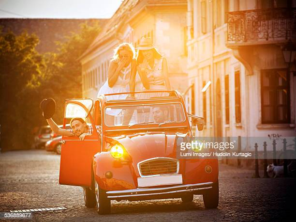 Young people in vintage car driving through city