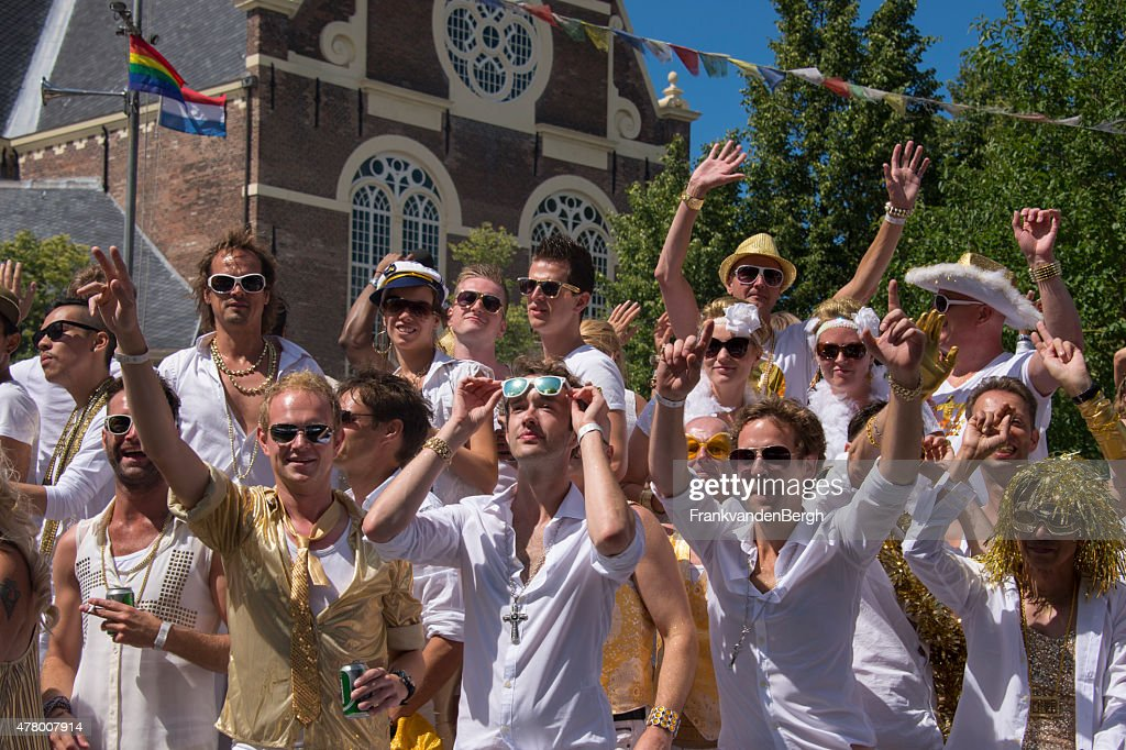 Young people in white outfits and rainbow accessories : Stock Photo
