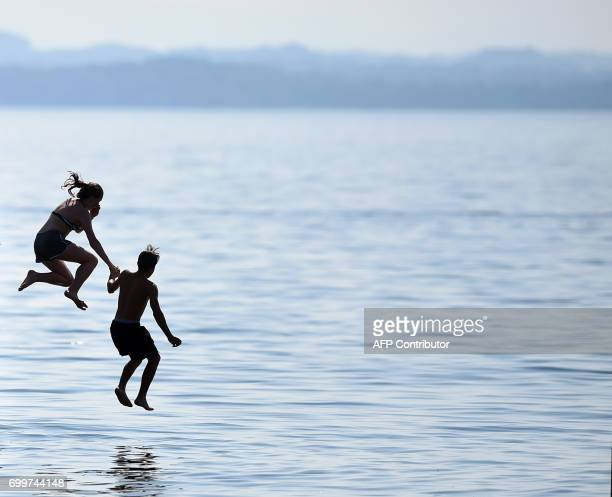 Young people jump in to the lake Chiemsee near the small Bavarian village Chieming southern Germany in front of the Alp mountain Kampenwand during...
