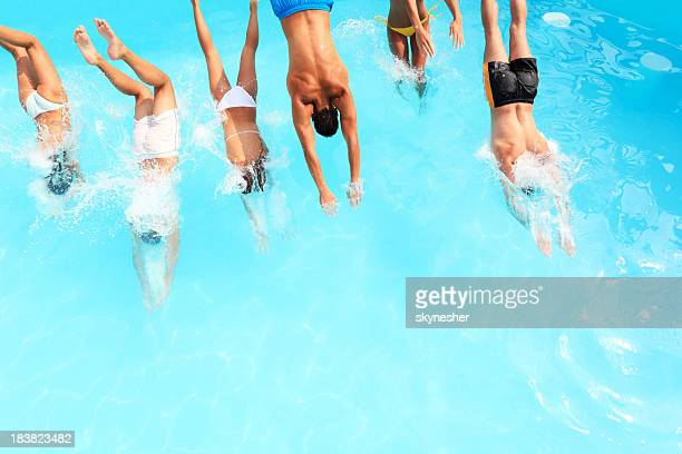 Young people jump into the pool.
