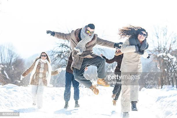 young people jumping and having fun in the snow - abiti pesanti foto e immagini stock