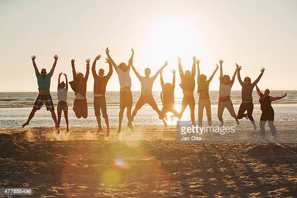 Young people jumping at the beach of St.Peter-Ording in Germany