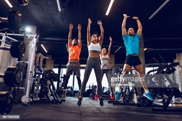 jeunes gens sautant pendant les cours de conditionnement physique au gym - sport d'équipe photos et images de collection