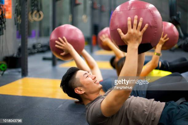young people lifting exercise ball in exercise class - medicine ball stock pictures, royalty-free photos & images