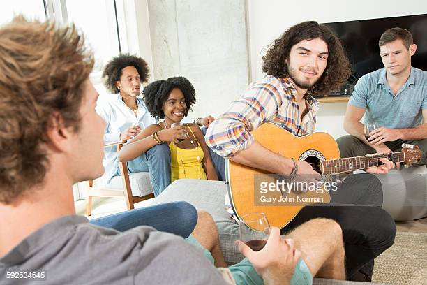 Young people listen to friend playing guitar.
