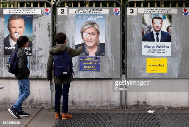 Young people look at graffitied official campaign posters of Marine Le Pen French National Front and political party leader Emmanuel Macron head of...