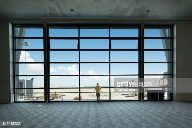 young people look at the airplane taking off at shagnhai pudong international airport - flughafenterminal stock-fotos und bilder