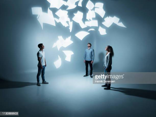 young people looking at flying paper - wisdom stock pictures, royalty-free photos & images