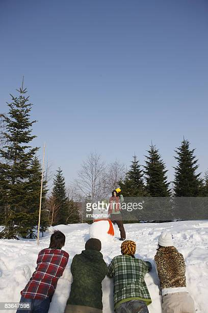 Young people looking at snowman