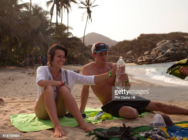 Young people lounging and laughing on the beach of Cabo San Juan on holiday in Tayrona National Natural Park a Colombian national park on the...
