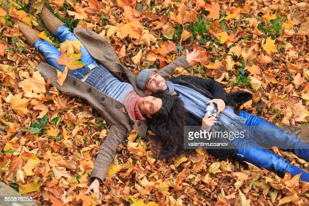 jeunes, couchée sur l'automne feuilles tapis - lying down photos et images de collection