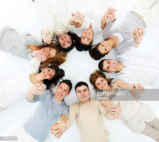 Young people lying in a circle with united hands.