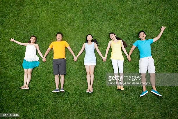 young people lying on meadow