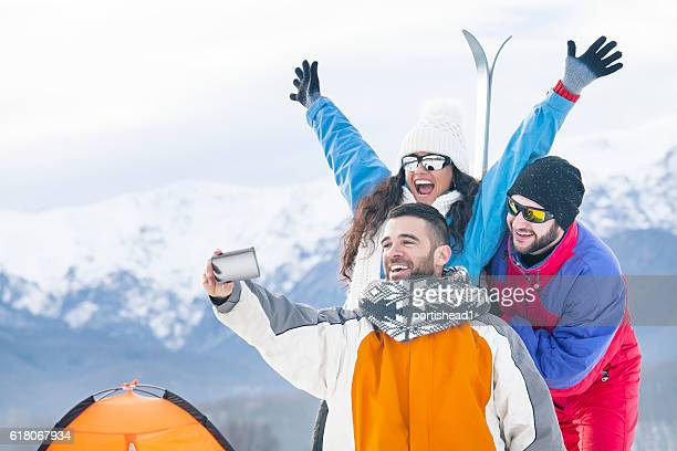 Young people making selfie on top of the snow mountain