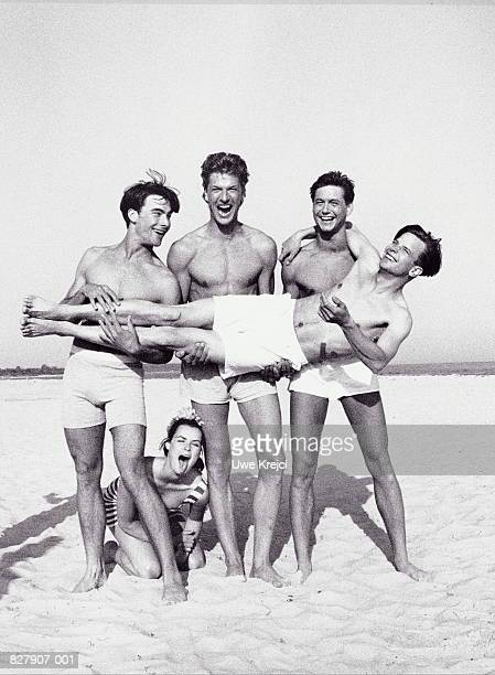 Young people on beach,men holding friend,woman kneeling in sand (B&W)