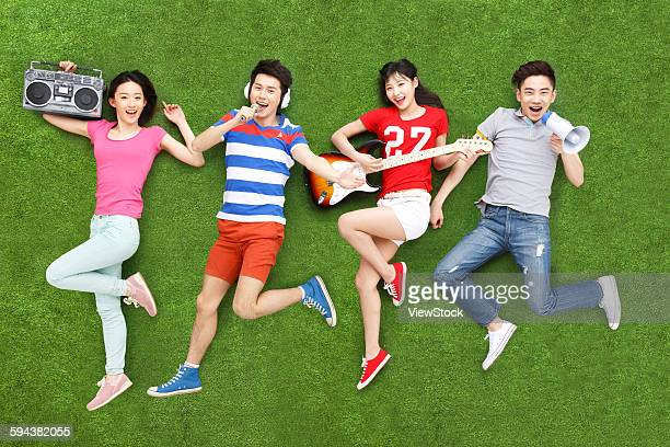 Young people on grass playing guitar and singing