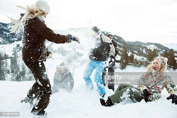 young people on winter holiday, snowfight - wintersport stock-fotos und bilder
