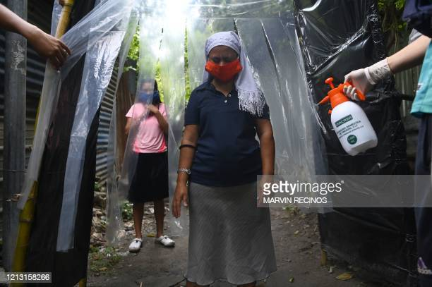 Young people organized in the Tineti community disinfect neighbors as they enter borough in San Salvador on May 15 amid the coronavirus pandemic