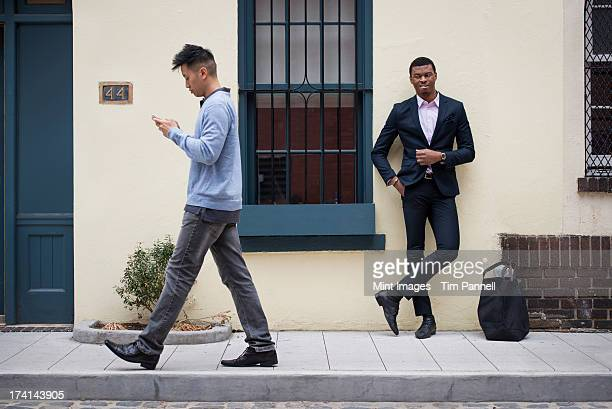 young people outdoors on the city streets in springtime.  a man leaning against a wall and one walking past checking his phone. - moving past stock photos and pictures