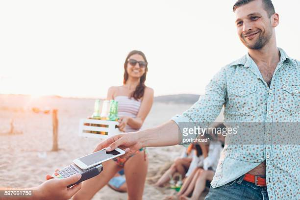 Young people paying with smart phone on beach