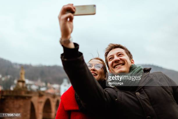 young people photographing with phone on a winter day in heidelberg - heidelberg germany stock pictures, royalty-free photos & images