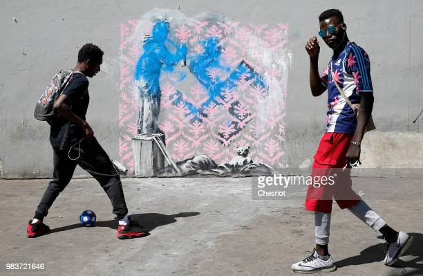 Young people play football in front of a damaged recent artwork attributed to street artist Banksy on June 25 2018 in Paris France Six frescoes...