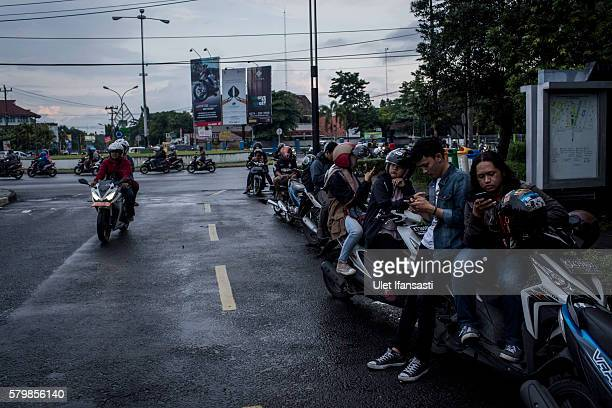 Young people play Pokemon Go game on smartphones in the street on July 23 2016 in Yogyakarta Indonesia 'Pokemon Go' which uses Google Maps and a...