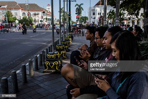 Young people play Pokemon Go game on smartphones on July 24 2016 in Yogyakarta Indonesia Pokemon Go which uses Google Maps and a smartphone has been...
