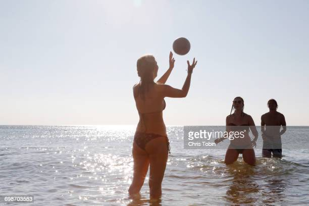 Young people playing ball in water at beach