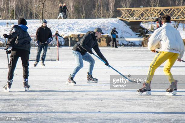 Young people playing ice hockey. People in the Netherlands enjoy the week-long cold snowy weather with subzero temperatures resulting lakes, ponds...