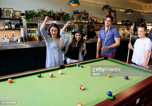 Young people playing pool in bar