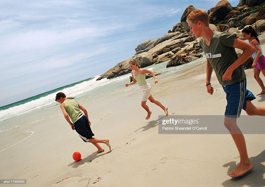 Young people playing soccer at the beach : Stockfoto