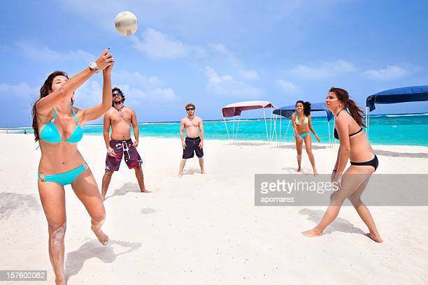 young people playing voleyball on a beach - beach volleyball stock pictures, royalty-free photos & images